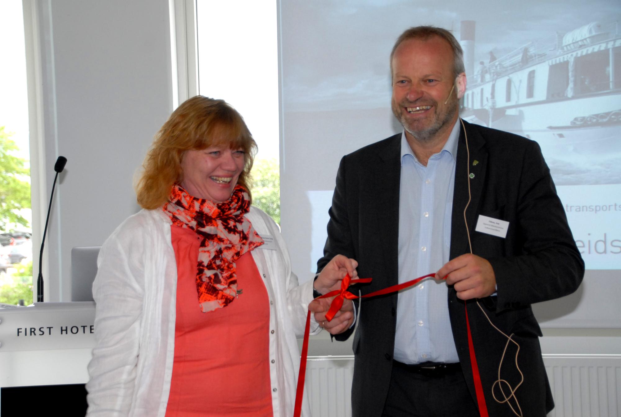 Fylkesråd for samfredsel i Hedmark Anne Karin Torp Adolfsen og fylkesvaraordfører i Oppland Ivar Odnes binder røde bånd for samarbeid