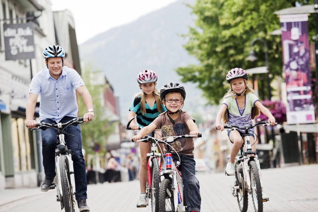 Familie på sykkeltur i Lillehammer sentrum.